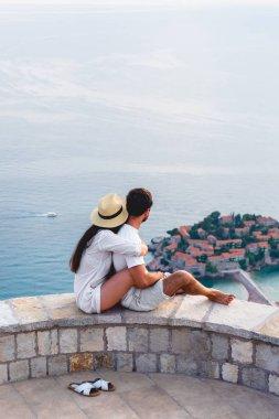 couple hugging and looking at island of Sveti Stefan in Adriatic sea, Budva, Montenegro