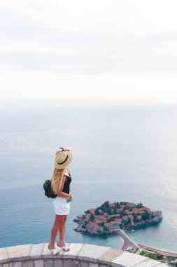 woman standing on viewpoint and looking at saint stephen island in Adriatic sea, Budva, Montenegro