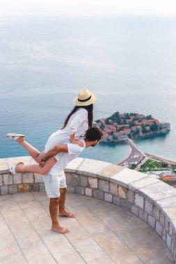 boyfriend giving piggyback to girlfriend at viewpoint near island of Sveti Stefan in Budva, Montenegro