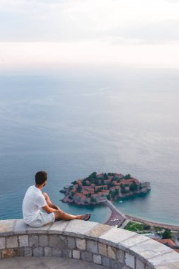 man sitting on viewpoint and looking at island of Sveti Stefan with hotel resort in Adriatic sea, Budva, Montenegro