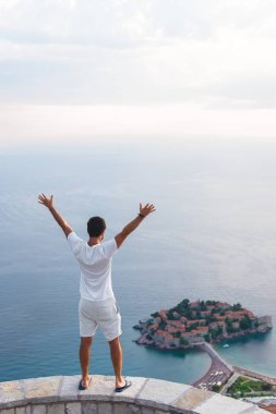 back view of man with raised hands looking at island of Sveti Stefan with hotel resort in Adriatic sea, Budva, Montenegro