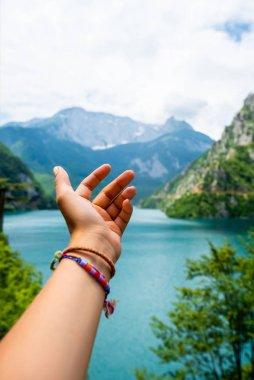 cropped image of woman reaching out hand for beautiful Piva Lake (Pivsko Jezero) in Montenegro