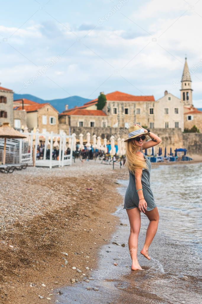 smiling woman walking on Ricardova Glava beach with Bell Tower on foreground in Budva, Montenegro