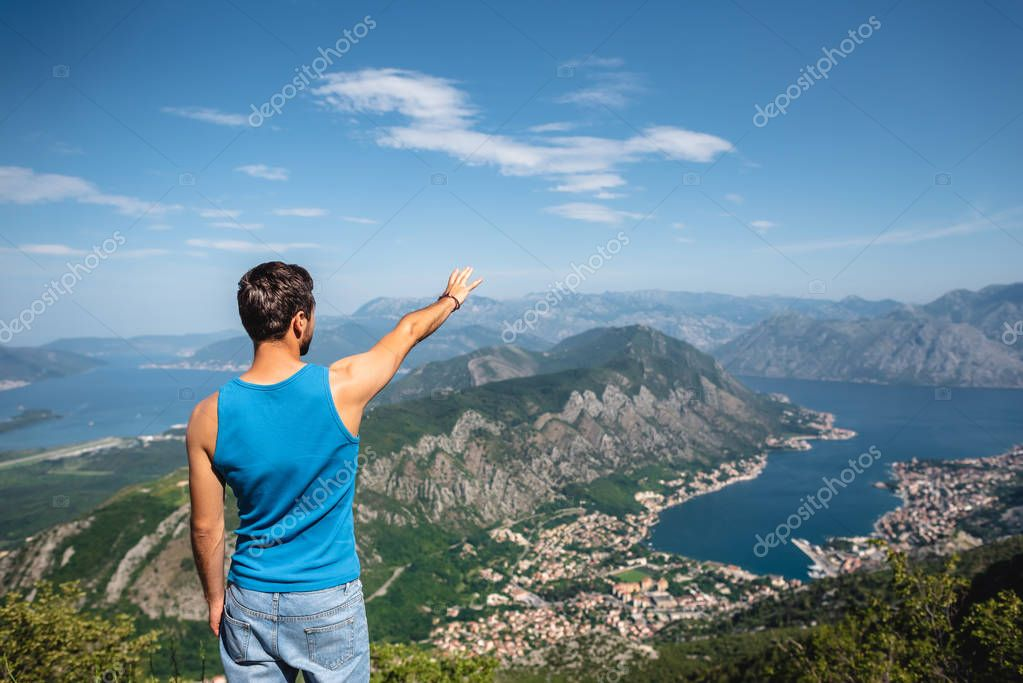 back view of man reaching out hand for Kotor bay and Kotor town in Montenegro