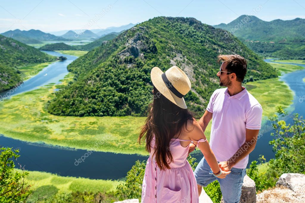 couple in pink clothes holding hands and looking at Crnojevica River in Montenegro