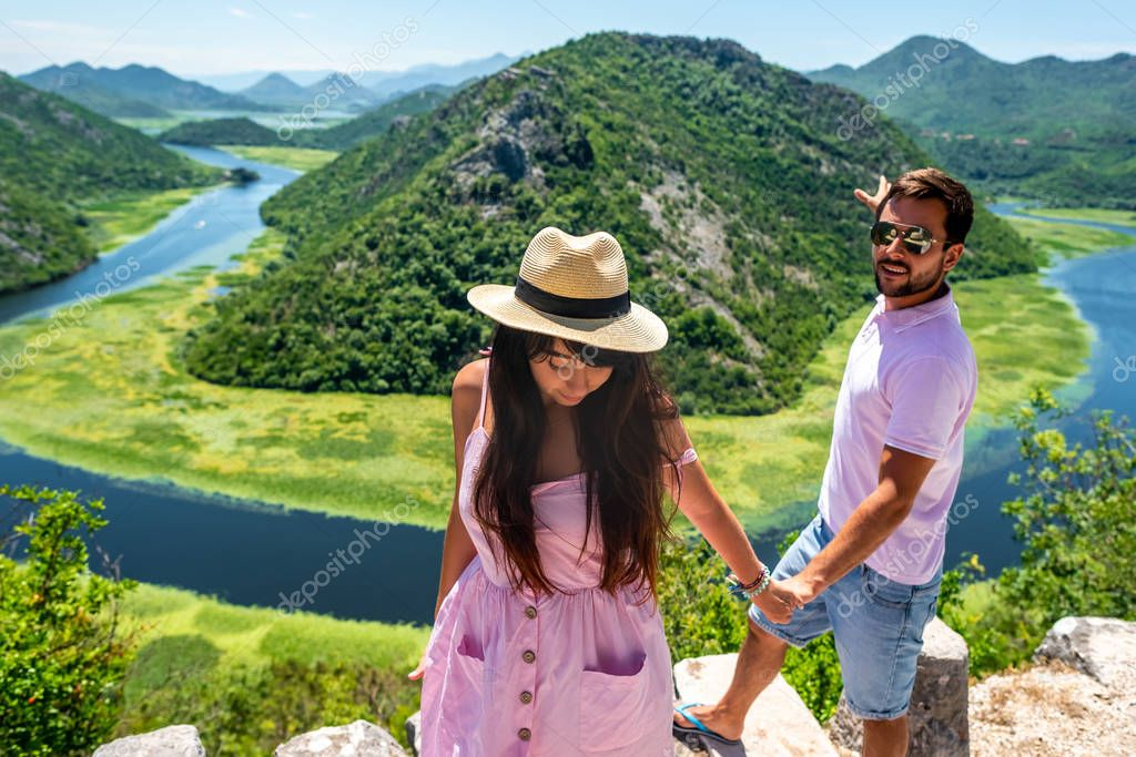 couple in pink clothes holding hands near Crnojevica River (Rijeka Crnojevica) in Montenegro