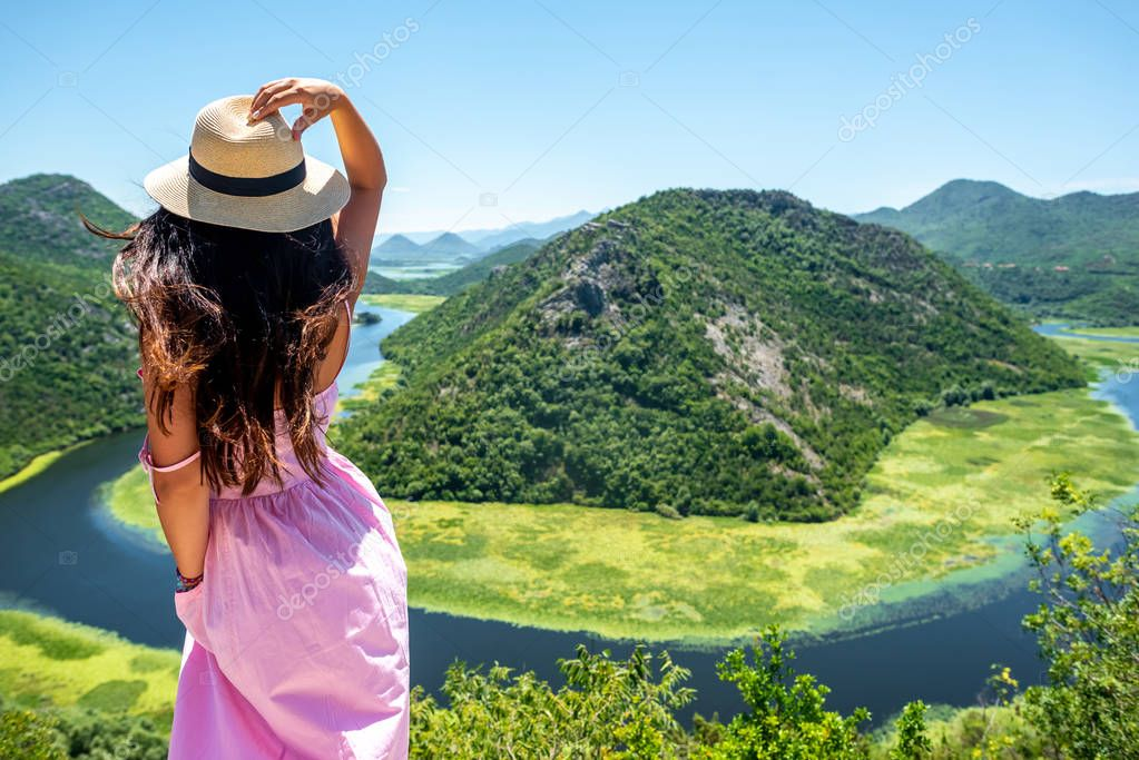 back view of woman in pink dress touching hat near Crnojevica River (Rijeka Crnojevica) in Montenegro