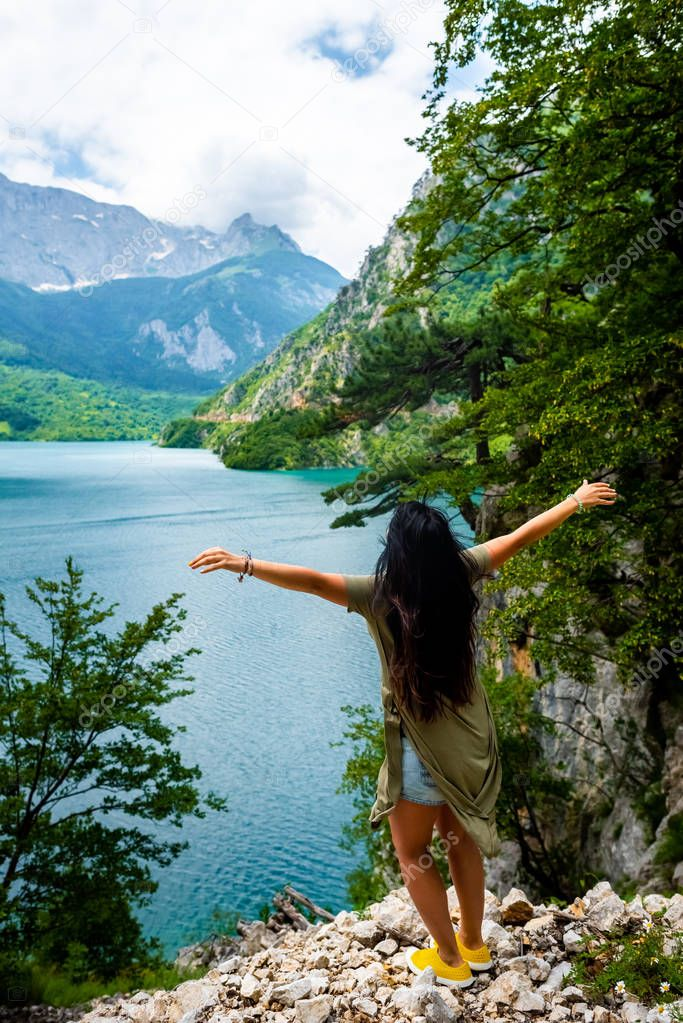 back view of woman standing with open arms near Piva Lake (Pivsko Jezero) in Montenegro