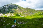 back view of woman standing on stone and looking at mountains in Durmitor massif, Montenegro