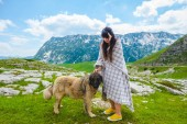 Photo beautiful woman in blanket palming fluffy dog on valley in Durmitor massif, Montenegro