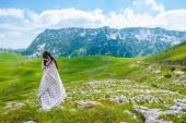 Fotografie krásná žena stojící zabalená v dece na údolí v masivu Durmitor, Černá Hora