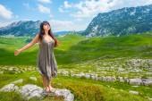 krásná žena stojící se zavřenýma očima a otevřenou náručí na kámen v údolí v masivu Durmitor, Černá Hora