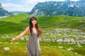 atraktivní žena stojící se zavřenýma očima a otevřenou náručí na údolí v masivu Durmitor, Černá Hora