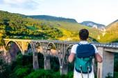 zadní pohled na Turistický batoh při pohledu na Tara most v Černé hoře