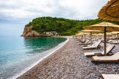 Fotografie sun loungers on empty beach of adriatic sea in Budva, Montenegro