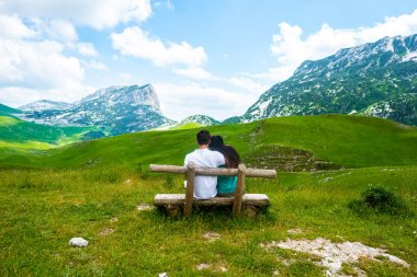Back view of couple sitting on wooden bench and looking at mountains in Durmitor massif, Montenegro stock vector