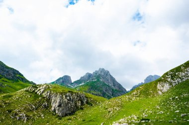 rocky mountains, green grass and cloudy sky in Durmitor massif, Montenegro