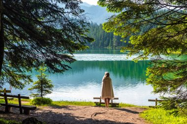 back view of woman in blanket looking at beautiful glacial Black Lake in Montenegro