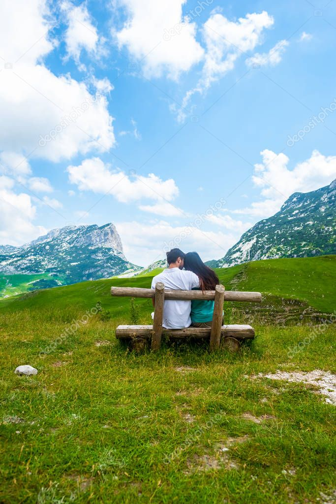 rear view of couple sitting on wooden bench and looking at mountains in Durmitor massif, Montenegro