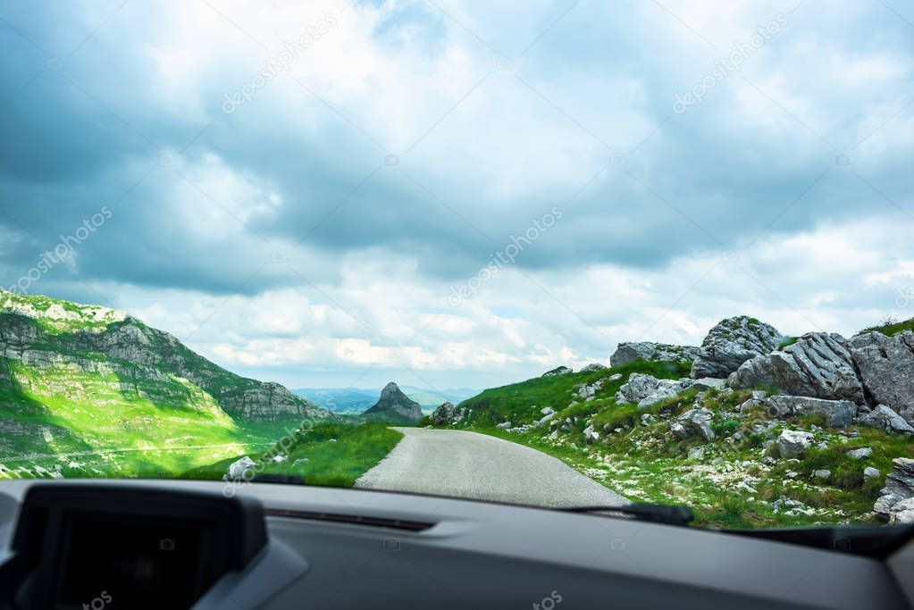 car on mountain road with cloudy sky in Durmitor massif, Montenegro