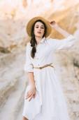 Fotografie okouzlující stylové dívka pózuje v bílých šatech a slaměný klobouk v pískového kaňonu