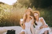 schöne glückliche Freunde mit Tassen Kaffee-Latte, die sitzen auf Boden mit Sonnenlicht