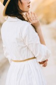 Photo cropped view of girl in white dress posing in sandy canyon