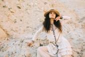 Fotografie stilvolle lockiges Mädchen posiert in Strohhut in sandigen canyon