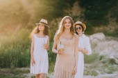 Fotografie attractive girls in straw hats holding coffee latte and walking in nature with sunlight