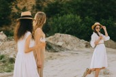 attractive stylish girls in straw hats walking in nature with plastic cups of coffee latte