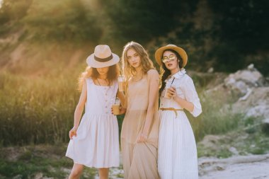beautiful girls in straw hats holding plastic cups with coffee latte