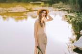 Fotografie krásná blondýnka v elegantní šaty a slaměný klobouk pózuje u jezera