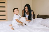 Fotografie happy young mother and child playing with bichon dog while sitting on bed at home