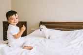 Fotografie entzückende kleine Kind Essen Cookie mit Bichon-Hund auf Bett