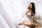 Fotografie happy young mother embracing her baby boy while sitting on floor at home