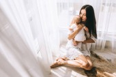 Fotografie happy young mother kissing her baby while sitting on floor at home