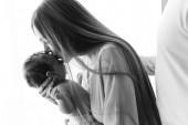 černobílý obraz ženy líbat její malý chlapeček, zatímco otec stál za doma