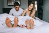 Photo selective focus of legs of family with infant son under blanket in bed at home