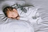 imádnivaló baba kisfiú ruha alszik az ágyban otthon szárnyakkal