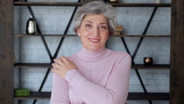 Lächelnd Reife grauhaarige Frau mittleren Alters blickt in die Kamera, eine glückliche alte Dame posiert zu Hause