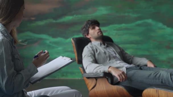 Egy mentális egészségügyi szakember jegyzetel, amikor a beteg problémákról beszél, miközben a kanapén fekszik.