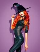 Halloween. sexy Hexe mit hellem Make-up und langen roten Haaren. schöne junge Frau posiert in Hexen sexy Kostüm über violettem Hintergrund