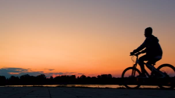 A teenager early in the morning at dawn or in the evening at sunset on a bicycle rides past a river or lake. Silhouette of a bicyclist guy.