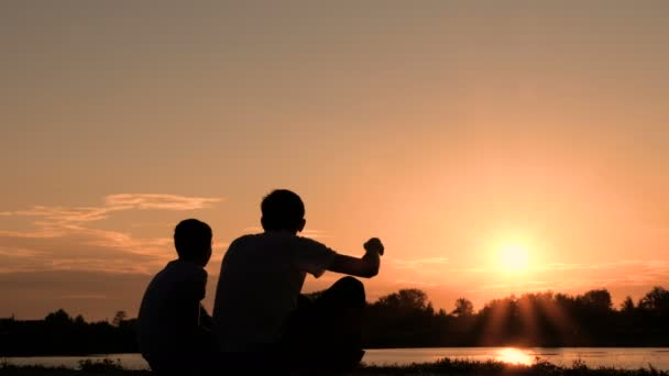 Father and son are sitting on the waterfront and watch the sunrise or sunset. Silhouette of two people communicating on the bank of a river or lake.