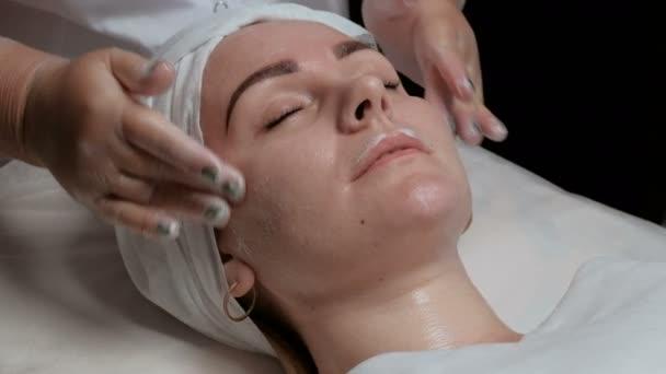 Wooman v salonu krásy roztomilý úsměv během obličejové čistící procedury. Kosmetička v průhledné rukavice distribuuje smetany a masáže na čelo, tváře a bradu, tváře klientů