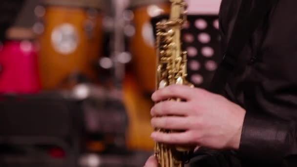 Közeli kép: a kezében egy szaxofonos, a szoprán szaxofon. A zenész egy fekete póló zenél egy fúvós hangszer. Jazz koncert.