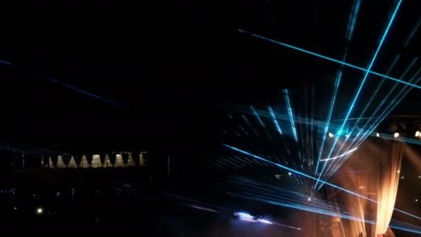Megnyitása a függöny a színpadon alatt egy lézer-show, az utcán. Absztrakt tarka sugarak ragyog éjjel.