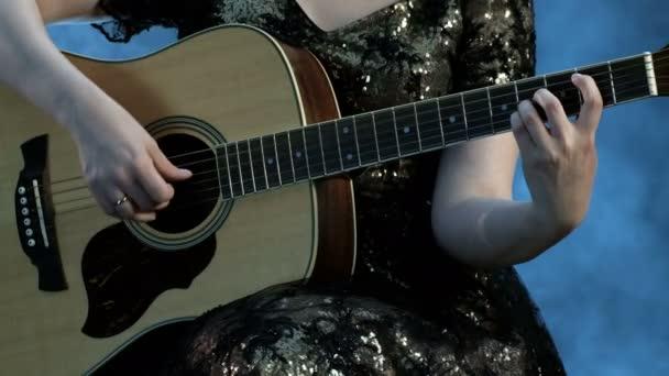 Dívka ve večerních šatech hraje 6 strunné akustické kytary. Pravá ruka se dotýká struny, levá ruka drží akordy na hmatníku. Kouř na pozadí. Den hudby.