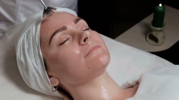 Eine professionelle Kosmetikerin streicht dem Mädchen einen letzten Pinselstrich auf die Stirn. das Verfahren zur Anwendung eines transparenten Gels mit einem Pinsel auf das Gesicht des Kunden im Schönheitssalon. eine Kerze brennt.