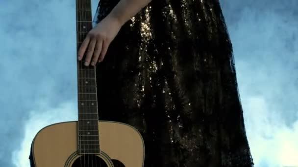 A lány ujjai a húrok közelről. A női kéz fut, az alulról felfelé a fretboard az akusztikus gitár. Nap a zene.